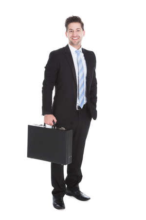 Full length portrait of young businessman with suitcase over white background photo