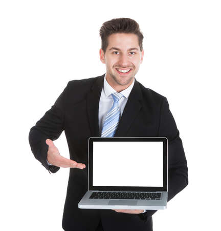 laptop stand: Portrait of confident mid adult businessman displaying laptop over white background