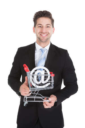 carretilla de mano: Retrato de joven hombre de negocios con la carretilla de mano y de Internet s�mbolo m�s de fondo blanco Foto de archivo