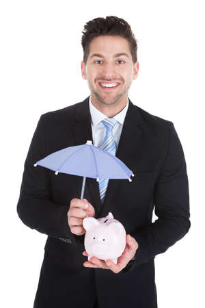 sheltering: Portrait of smiling young businessman sheltering piggybank with umbrella over white background