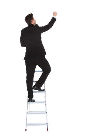 Full length rear view of young businessman climbing career ladder over white background