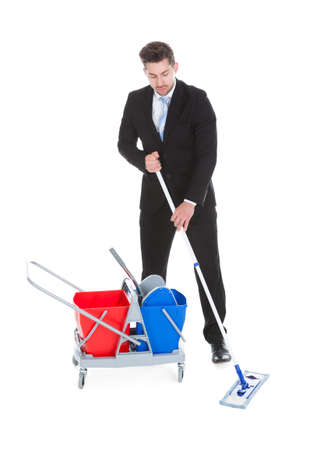 downsized: Full length of sad young businessman mopping over white background