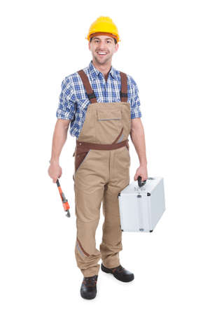 studio happy overall: Full length portrait of confident young male worker with wrench and toolbox over white background