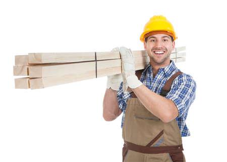 白い背景の上に木の板を運ぶ若い肉体労働者の完全な長さの肖像画