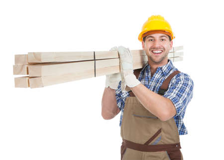 Full length portrait of young manual worker carrying wooden planks over white background Stok Fotoğraf