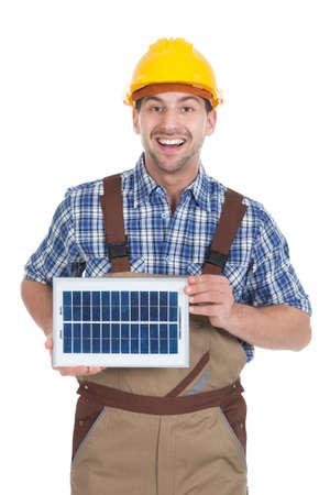 Portrait of confident repairman holding solar panel over white background photo