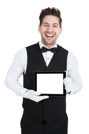 butler: Portrait of young butler displaying digital tablet over white background Stock Photo