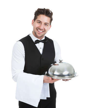 Portrait of confident waiter holding domed tray isolated over white background photo
