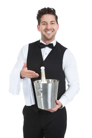 alcohol server: Portrait of confident young waiter holding ice bucket with champagne bottle over white background