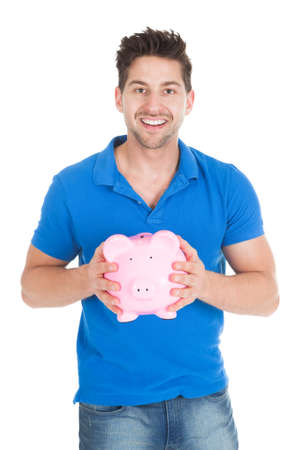 coinbank: Portrait of young man holding piggybank isolated over white background Stock Photo