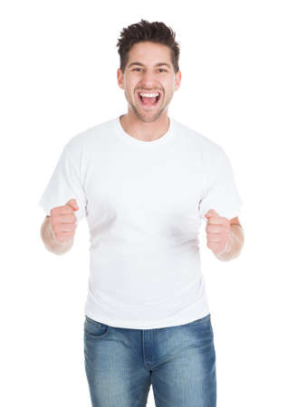 Portrait of excited young man with clenching fists isolated over white background photo
