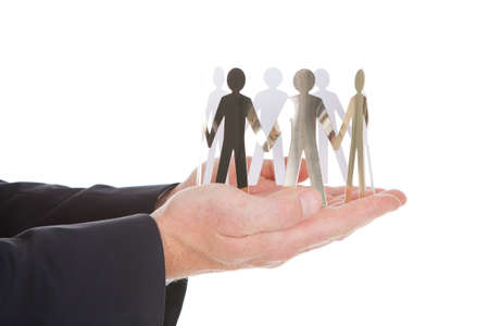 Closeup of businessmans hands with paper people representing unity over white background photo