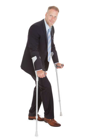 Full length portrait of mid adult businessman walking with crutches over white background photo