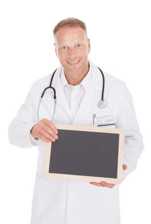 Portrait of smiling mid adult male doctor holding blank slate over white background photo