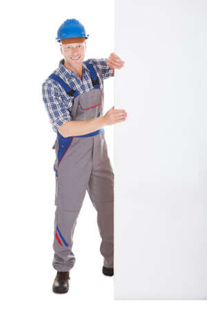 studio happy overall: Full length portrait of confident young manual worker holding billboard over white background Stock Photo