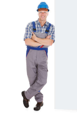 tradesman: Full length portrait of happy manual worker standing arms crossed over white background Stock Photo