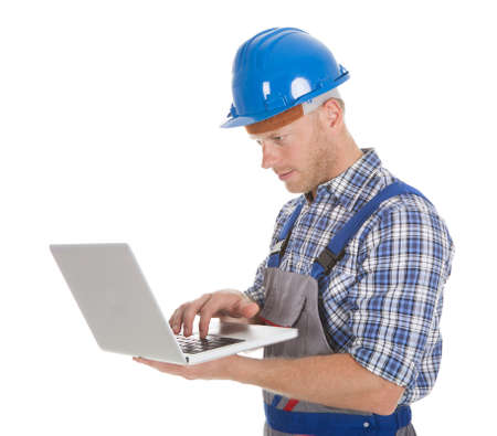 Smiling young manual worker using laptop over white background photo