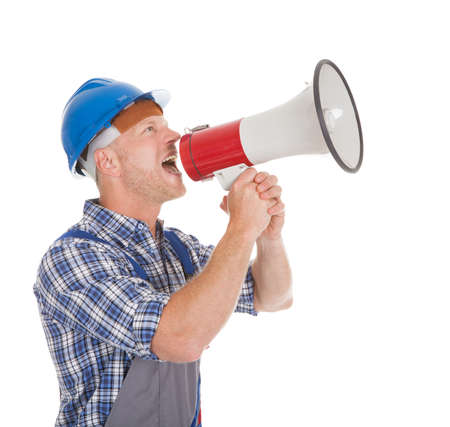 tradesmen: Full length of mid adult manual worker speaking into megaphone over white background