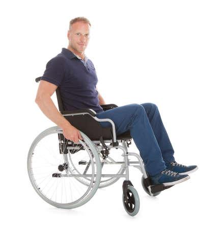paraplegico: Retrato de cuerpo entero del hombre discapacitado en silla de ruedas sobre fondo blanco Foto de archivo