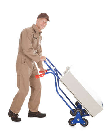 delivery man: Full length portrait of delivery postman pushing machine on cart over white background