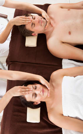 High angle view of relaxed young couple receiving head massage at beauty spa photo