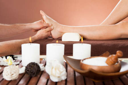Cropped image of male therapist massaging female customers foot at beauty spa photo