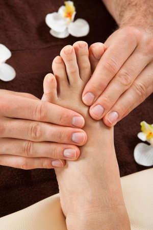 reflexologie: Gros plan de thérapeute homme donnant un massage des pieds à la clientèle féminine au salon de beauté