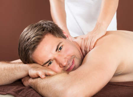 color therapist: Young man receiving back massaging in spa