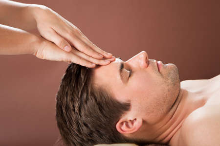 Side view of relaxed young man receiving forehead massage in spa photo