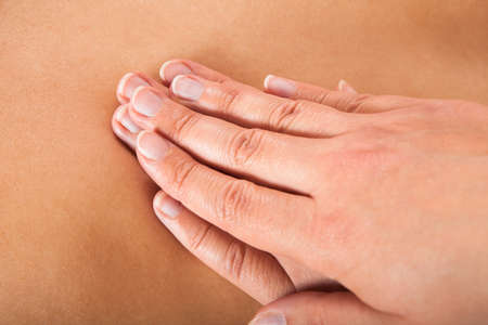 giving back: Closeup of female therapist giving back massage to woman at beauty spa Stock Photo