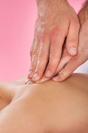 acupressure: Closeup of male therapist massaging female customers back at beauty spa