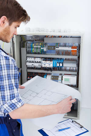 fusebox: Cropped image of male technician analyzing blueprint in front of fusebox