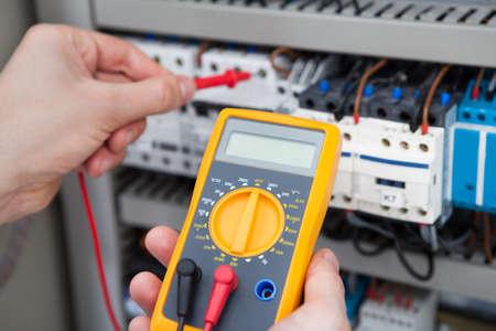test probe: Immagine ritagliata di maschio elettricista esaminare fusebox con isolamento digitale di resistenza tester