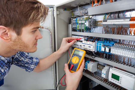 Side view of male technician examining fusebox with digital insulation resistance tester photo