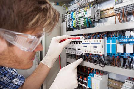 electricista: Recorta la imagen de macho ingeniero eléctrico caja de fusibles que examina con el multímetro Foto de archivo