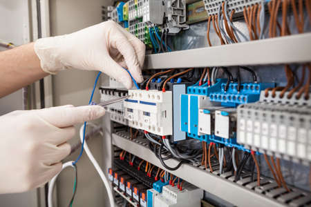 fuse box: Cropped image of male technician repairing fusebox
