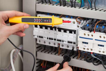 Kadrowania obrazu męskiej elektryk bada skrzynki bezpieczników z testera