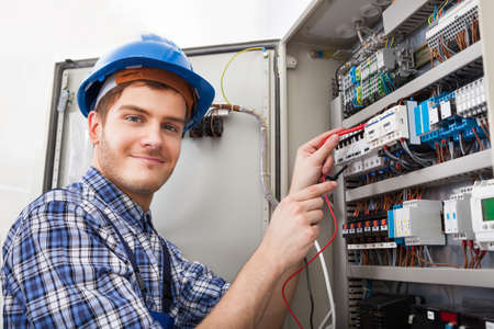 technician: Side view of male technician examining fusebox with multimeter probe