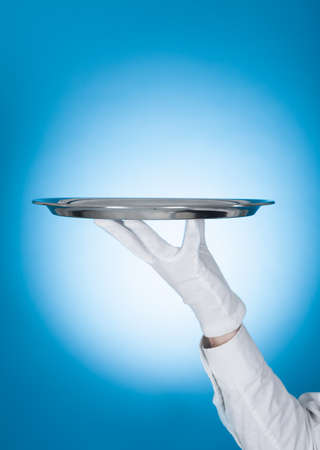 Cropped image of waiter carrying empty tray over blue background photo