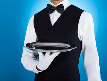 Midsection of young waiter carrying empty tray over blue background photo