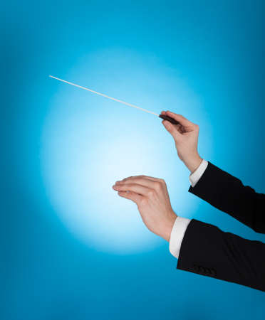 choral: Cropped image of musician holding baton against blue background