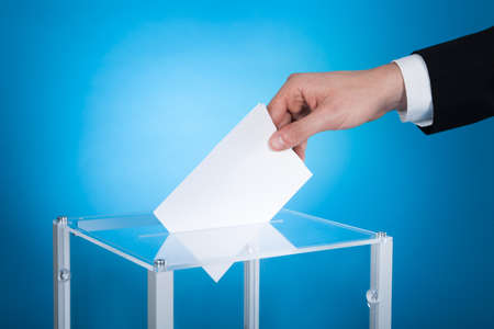 ballot box: Cropped image of businessman putting paper in election box against blue background Stock Photo