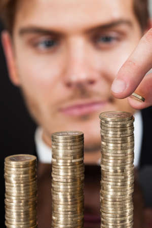 Young businessman stacking coins at desk against black background photo