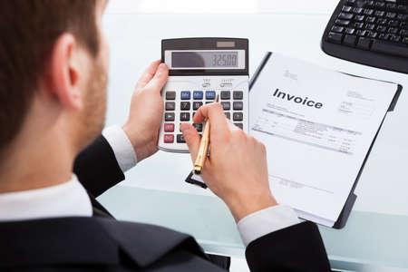 Bijgesneden afbeelding van zakenman het berekenen van de factuur bij de balie in kantoor Stockfoto