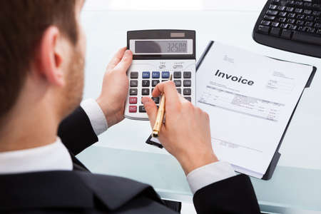 Cropped image of businessman calculating invoice at desk in office