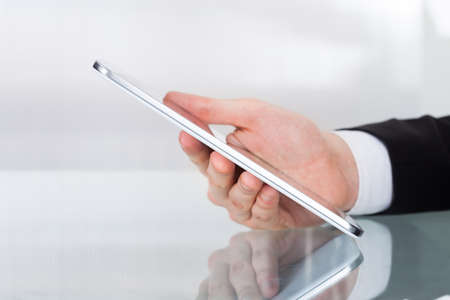 Cropped image of businessman holding digital tablet at desk in office photo