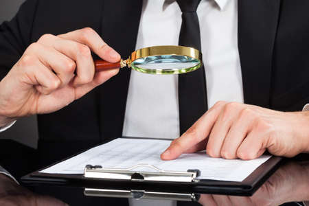 magnifying glass man: Midsection of young businessman analyzing document with magnifying glass at desk