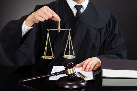 Midsection of male judge holding weight scale at desk against black background photo