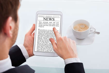 cropped image: Cropped image of businessman reading news on digital tablet at desk in office
