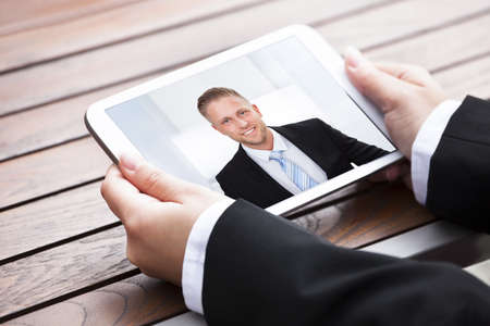 conferencing: Cropped image of businesswoman video conferencing with colleague on digital tablet outdoors
